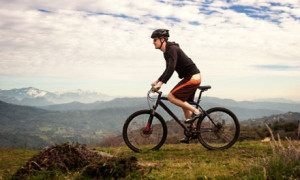 Man on bike cycling over hills