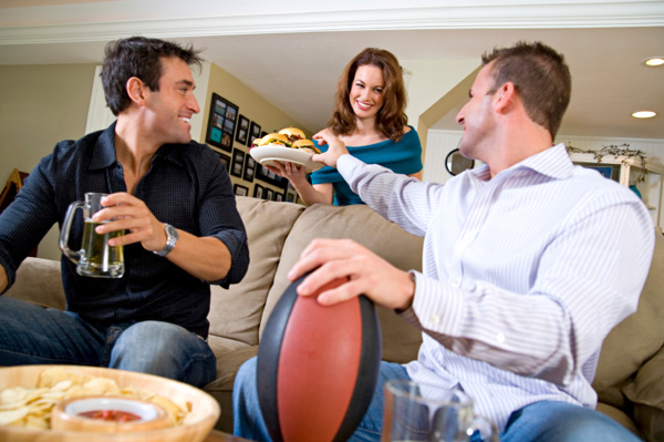 woman-serving-snacks-to-husband-and-friend-watching-football